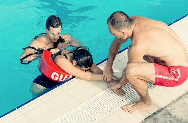 Lifeguards in training - Rescuing female victim from public swimming pool